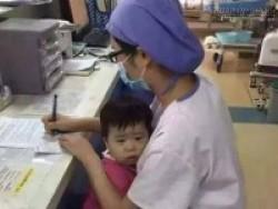 Nữ y tá vừa bế trẻ mồ côi vừa làm việc gây xúc động