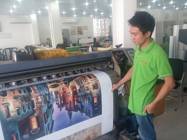 Nhân viên đứng máy in kỹ thuật số trực tiếp giám sát đơn hàng in tranh canvas