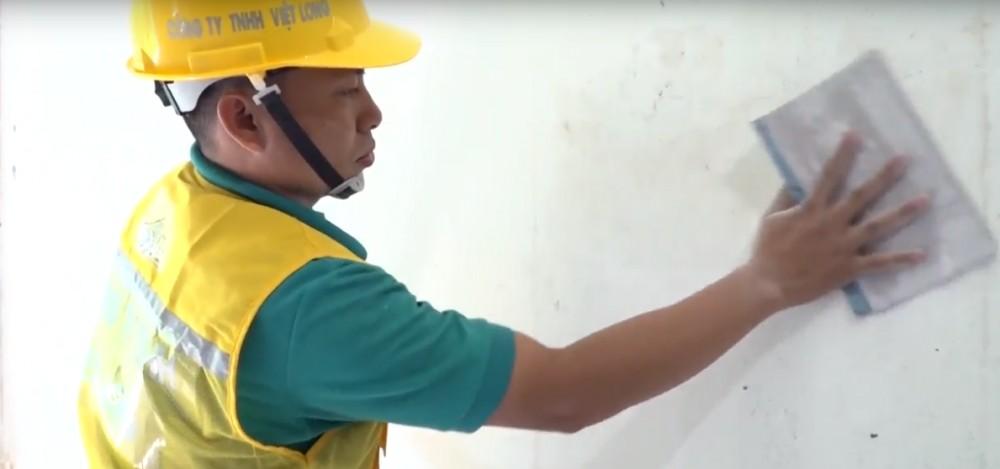Sử dụng giấy nhám để chà phẳng bề mặt tường.
