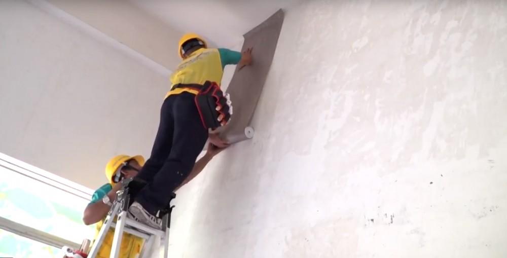 Cầm cả cuộn vải đưa lên bề mặt tường và xả từ từ cuộn vải dán tường