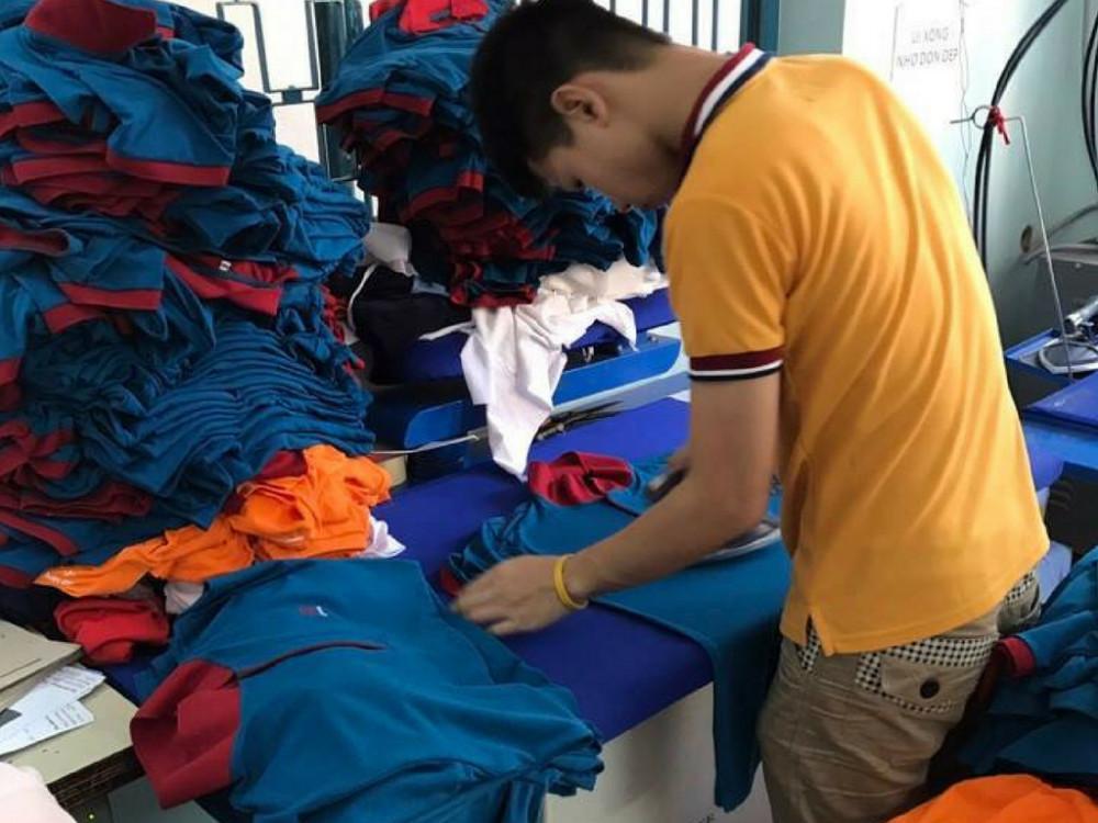Thợ ủi giúp làm phẳng cáo - chuẩn bị cho khâu đóng gói bao bì gửi khách hàng