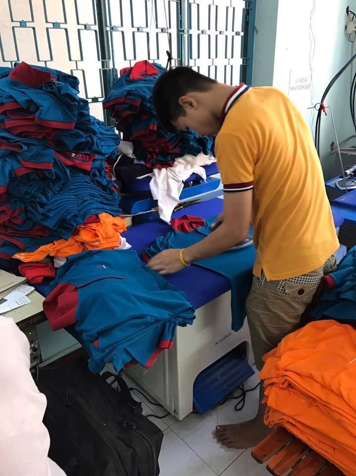 Thợ ủi với công đoạn ủi áo thun cá sấu - xưởng may áo thun cá sấu TPHCM